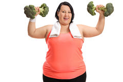Overweight woman exercising with broccoli dumbbells Royalty Free Stock Photography