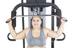 Overweight woman exercising on a cable machine Royalty Free Stock Photography