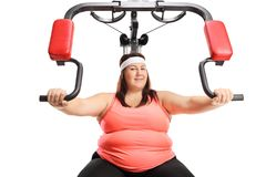 Overweight woman exercising on a multifunctional machine Stock Photos