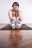Overweight woman exercising/stretching at home Stock Image