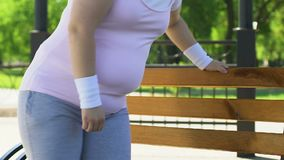 Overweight woman exhausted after tiresome workout outdoors, resting on bench stock video footage