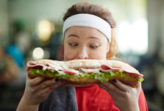 Overweight Woman with Fast Food Obsession. Closeup portrait of young obese woman holding big fattening sandwich in front of her face royalty free stock photography