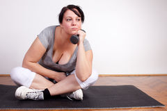 Overweight woman is fed up and tired of exercising Royalty Free Stock Photography