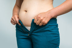 Overweight woman getting dressed wearing jeans Stock Images
