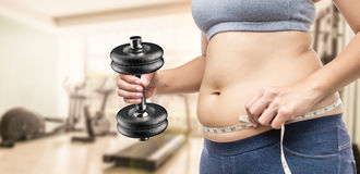Overweight woman hand holding tape measure and dumbbell Stock Images