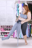 Overweight woman with her old jeans. Full length of blonde woman trying to wear her old jeans at home with wardrobe background stock photo