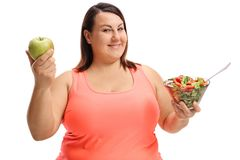 Overweight woman holding an apple and a salad. Isolated on white background Stock Photography