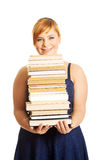 Overweight woman holding books. Overweight woman in skirt holding heavy books Royalty Free Stock Photography