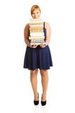 Overweight woman holding books. Overweight woman in skirt holding heavy books Royalty Free Stock Photos