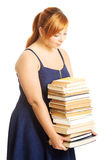 Overweight woman holding books. Overweight woman in skirt holding heavy books Royalty Free Stock Image