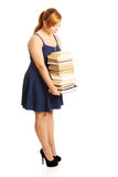 Overweight woman holding books. Overweight woman in skirt holding heavy books Stock Photos