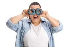 Overweight woman holding donuts infront of her eyes stock photography