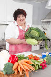 Overweight woman holding salads - cooking at home. Royalty Free Stock Photo