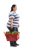 Overweight woman holding a shopping basket and waiting in line Stock Photo