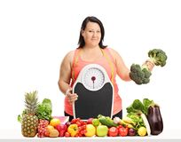 Overweight woman holding a weight scale and a broccoli dumbbell Royalty Free Stock Photography