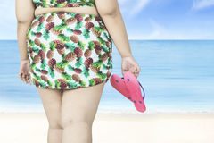 Overweight woman holds sandals on beach Stock Photography