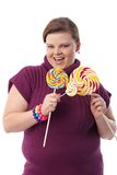 Overweight woman with huge lollipops smiling Stock Image