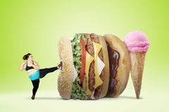 Overweight woman kicking fast foods. Diet concept. Overweight woman refuses to eat fast food and kicking a big hamburger and ice cream, shot with green screen Royalty Free Stock Photo