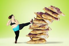 Overweight woman kicking pizza. Diet concept. Overweight woman avoids to eat junk foods by kicking pizza. Shot with green screen background Royalty Free Stock Photography