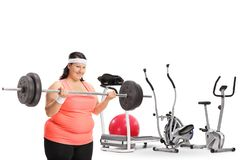Overweight woman lifting a barbell in front of exercise machines. Isolated on white background Royalty Free Stock Photography
