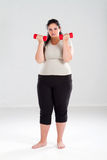 Overweight woman lifting weights Stock Photo