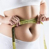 Overweight woman measuring her fat belly. Woman with overweight measuring her fat belly. Obesity concept. Over gray background Royalty Free Stock Image