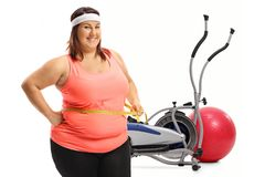 Overweight woman with a measuring tape. In front of a cross trainer machine and a pilates ball isolated on white background Stock Images