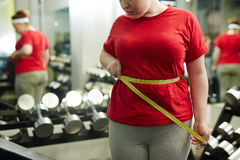 Overweight Woman Measuring Waist in Gym Royalty Free Stock Photography