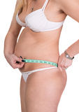 Overweight woman measuring waistline with centimete Royalty Free Stock Photography