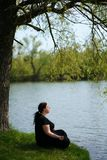 Overweight woman meditating outdoors stock photography