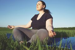 Overweight woman meditating at yoga mat outdoors. Body positive, yoga, meditation, tranquility, relax. Overweight woman meditating sitting at yoga mat outdoors stock image