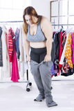 Overweight woman with old jeans at home Stock Photo