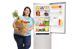 Overweight woman with a paper bag filled with fruit and vegetables leaning against an open fridge. Isolated on white background stock photography
