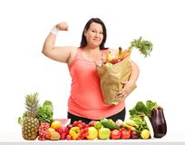 Overweight woman with a paper bag flexing her biceps behind a ta Stock Photography