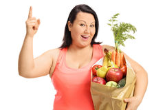 Overweight woman with a paper bag holding her finger up Stock Image