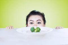 Overweight woman peeking broccoli Stock Photography