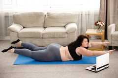 Overweight woman performs hyperextension exercise. Fitness trainer, internet sporting class, training online. overweight woman looking tutorial video performing royalty free stock images
