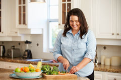 Overweight Woman Preparing Vegetables in Kitchen Stock Images