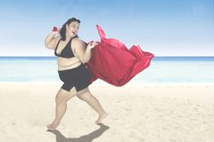 Overweight woman with red scarf at coast. Happy overweight woman running on the beach while holding a red scarf, shot at summertime Stock Photography