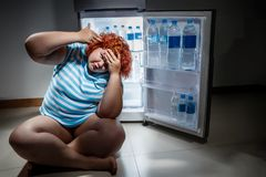 Overweight woman with  refregerator Royalty Free Stock Photography