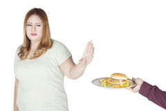 Overweight woman refusing burger on studio Royalty Free Stock Photo