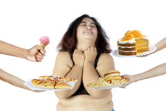 Overweight woman rejecting unhealthy food. Image of overweight woman rejecting unhealthy food offered by someone, isolated on white background stock photography