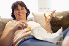 Overweight Woman Relaxing On Sofa Stock Photography