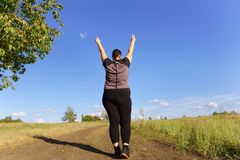 Overweight woman rising hands, view from the back royalty free stock photo