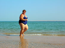 Overweight woman running on beach Royalty Free Stock Photos