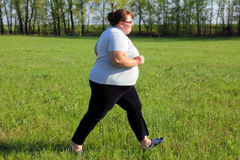 Overweight woman running on meadow Stock Image