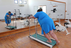 Overweight woman running on trainer treadmill. Fitness - overweight woman running on trainer treadmill Royalty Free Stock Photography