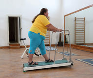 Overweight woman running on trainer treadmill Stock Images