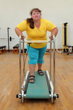 Overweight woman running on trainer treadmill Royalty Free Stock Photos