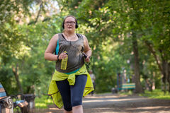 Overweight woman running. Weight loss concept. Overweight woman running in the park with a bottle of water listening to music. Weight loss concept Royalty Free Stock Photo